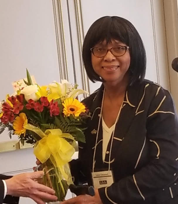 Former Executive Director Juliet Emanuel holding a bouquet of flowers
